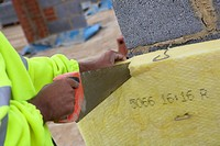 Bricklayer cutting insulation panels for cavity wall
