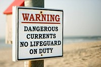 Warning sign on post at the beach with ocean in background