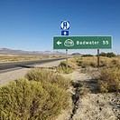 Road sign on side of desert road with direction to Badwater, Death Valley