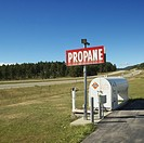 Propane tank with sign on side of rural road