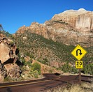 Curve caution sign on two lane road winding through rocky desert cliffs in Zion National Park, Utah