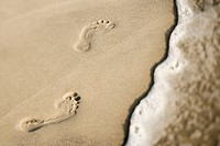 Footprints in sand next to wave