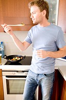 man tasting food in the kitchen