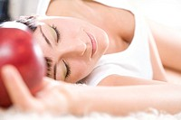 woman laying with apple in hand