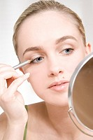 young woman putting on eyeliner