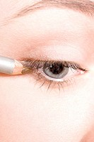 close_up of a woman puttiong on eyeliner