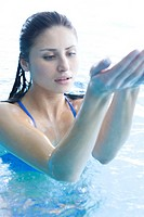 Young woman playing in swimming pool (thumbnail)
