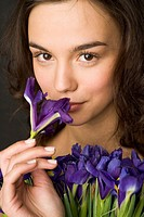 Young woman smelling blue iris (thumbnail)