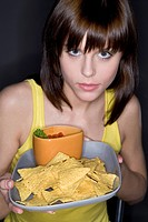woman eating tortilla chips with salsa