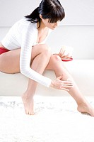 Young woman applying lotion on legs (thumbnail)