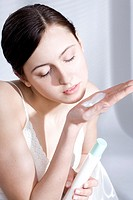 young woman iwth body milk on hand