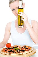 young woman pouring oil on pizza