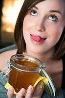 Woman eating honey (thumbnail)