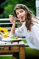 Woman eating on the terrace (thumbnail)