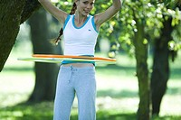Young woman hula hooping in park