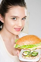 Young woman holding plate with sandwiches (thumbnail)