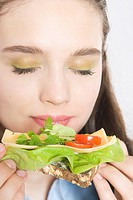 Young woman eating sandwich (thumbnail)