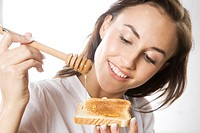 Young woman eating toast with honey