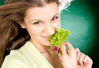 Young woman with salad leaf