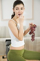 Young woman eating grapes (thumbnail)