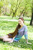 ginger girl sitting on grass
