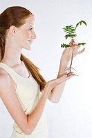 Young woman holding plant (thumbnail)