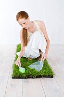 young woman celaning grass