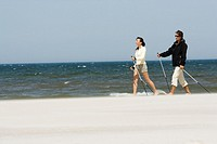 Couple hiking on beach (thumbnail)