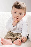Baby eating crisps on sofa