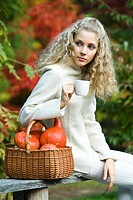 Young woman drinking tea in park (thumbnail)