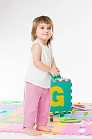toddler girl playing with letters and numbers