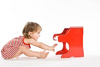 toddler girl playing on piano