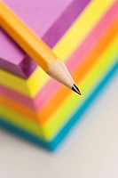 Close up of sharp pencil on stack of colorful sticky notes.