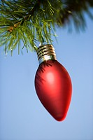 Red ornament hanging on Christmas tree branch against blue background