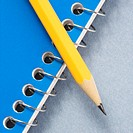 Sharp pencil placed on blue spiral bound notebook