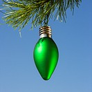 Green ornament hanging on Christmas tree branch against blue background.