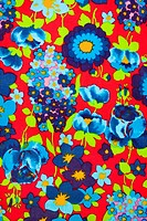 Close_up of vintage fabric with vibrant blue and turquois flowers printed on polyester