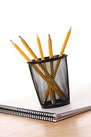 Pencils in pencil holder on top of spiral bound notebook