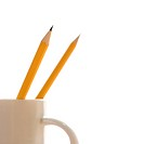 Two pencils in a coffee cup with pointed ends up
