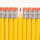 Even row of eraser ends of pencils except for one that has the pointed end up