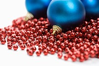 Still life of large blue Christmas ornaments and strings of red beads