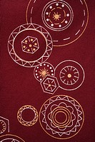 Close_up of maroon vintage fabric with white and yellow lines and shapes printed on polyester