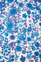 Close_up of woven vintage fabric with blue flowers and designs printed on cotton