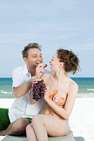 couple eating grapes on beach