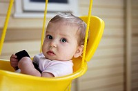Eight month old baby in swing