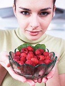 young woman holding bowl with raspberries