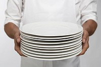 Chef holding stack of dinner plates mid section