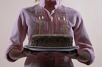 Woman carrying birthday cake close_up, midsection