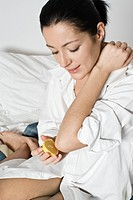 Woman putting lemon on elbow