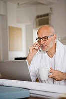 Mature man holding a cup of coffee and looking at a laptop